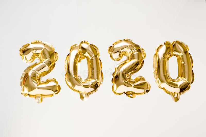 Happy New year 2020 celebration. Gold foil balloons numeral 2020 on white background stock images