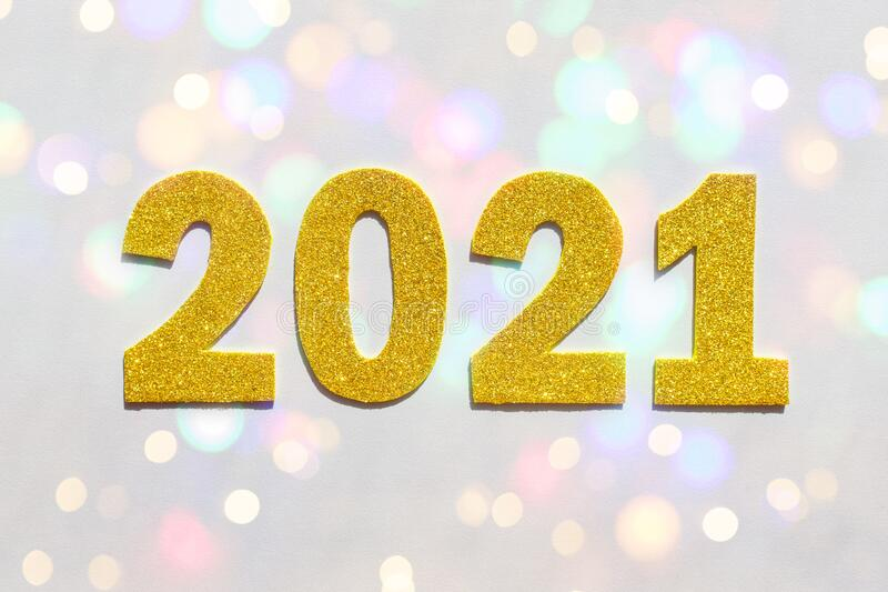 Happy New year 2021 celebration. Gold numeral 2021 and lights. Flat lay stock photo