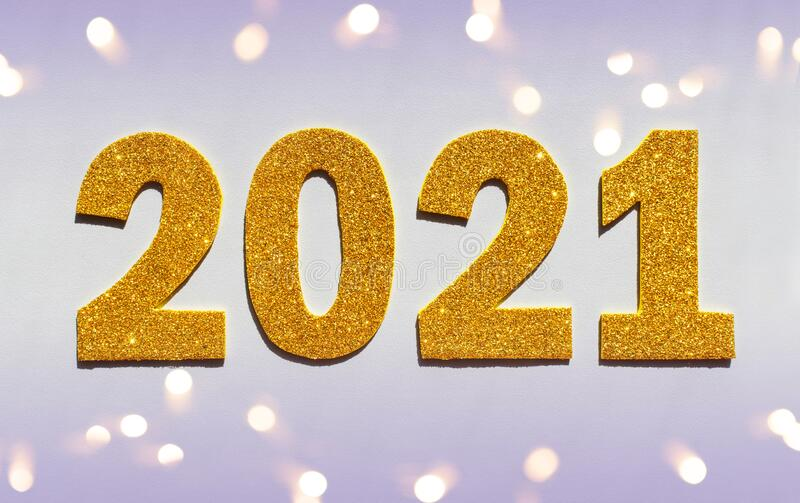 Happy New year 2021 celebration. Gold numeral 2021 and lights. Flat lay royalty free stock image