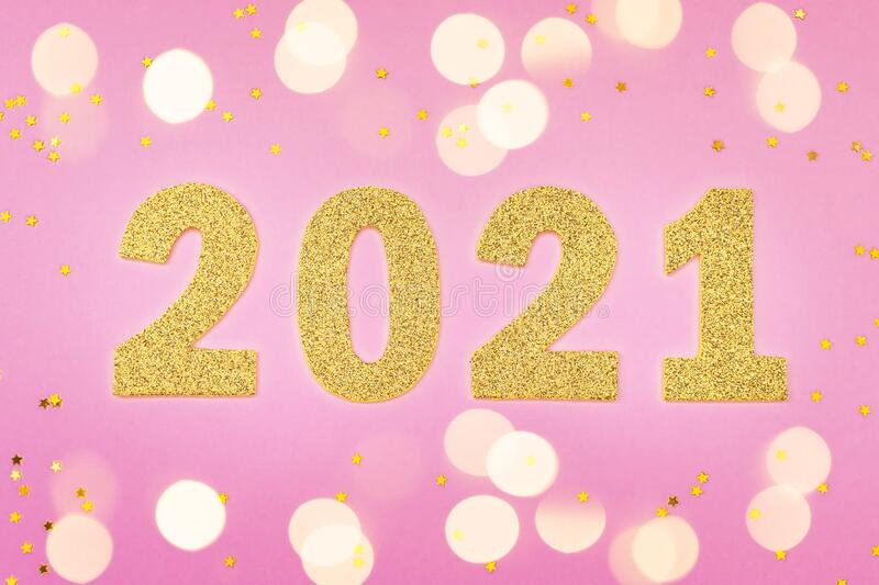 Happy New year 2021 celebration. Gold numeral 2021 and lights. Flat lay. Golden stars stock photo