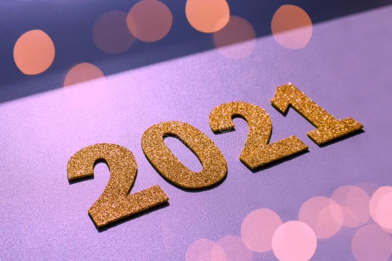 Happy New year 2021 celebration. Gold numeral 2021 and lights on purple background. Flat lay royalty free stock image