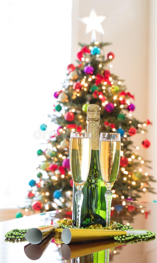 Happy New Year Celebration with Golden Champagne for two and bright Christmas tree in background stock photography