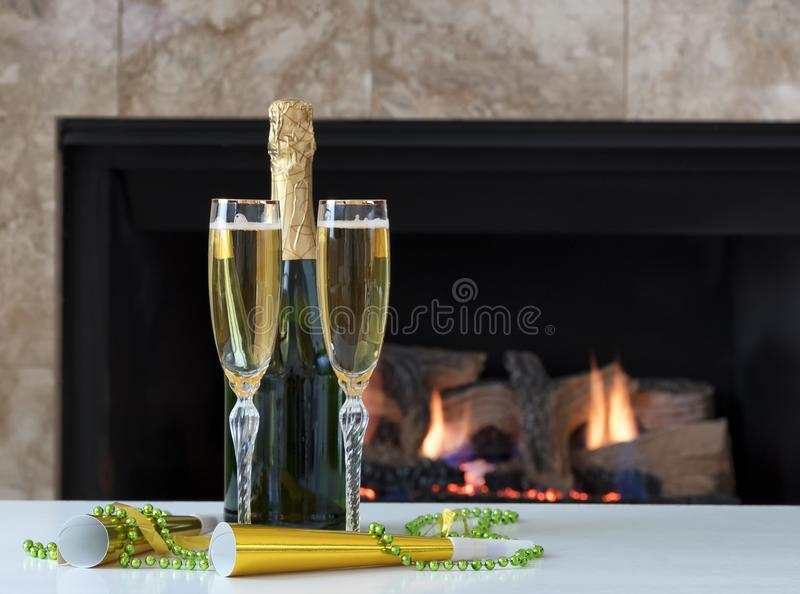 Happy New Year Celebration with Golden Champagne for two and glowing fireplace in background stock photo