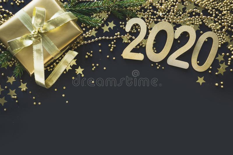 Happy New 2020 Year. Christmas border of golden gift box, decoration, shine stars and beads on black. Flat lay style. Happy New 2020 Year. Christmas border of royalty free stock photos