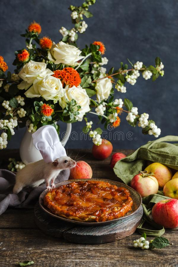 Happy New Year 2020. Christmas composition, symbol of the year. The rat is a cook by the apple pie royalty free stock photo