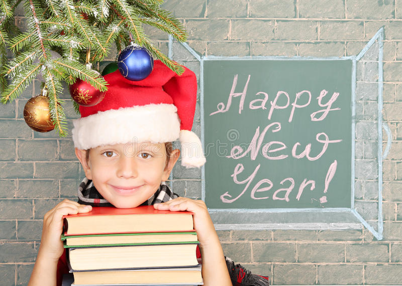 Happy New Year!. Christmas decoration, schoolboy and message on chalkboard Happy New Year royalty free stock image