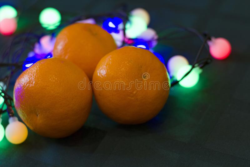 Christmas decoration tangerines on a dark background with lights. Background for design.Happy New Year 2020 stock photo
