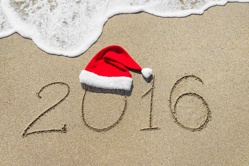 Happy new year 2016 with christmas hat on sandy beach royalty free stock photography