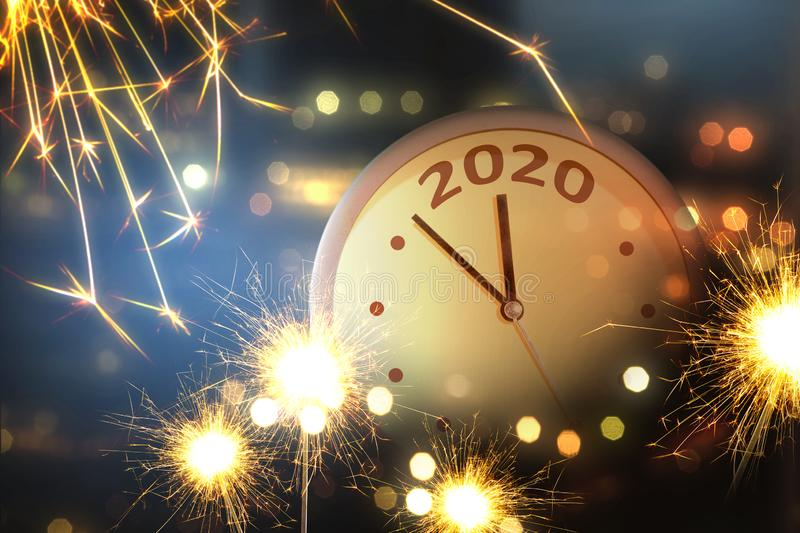 Happy New Year 2020. Clock with fireworks background. Happy New Year 2020 royalty free stock image