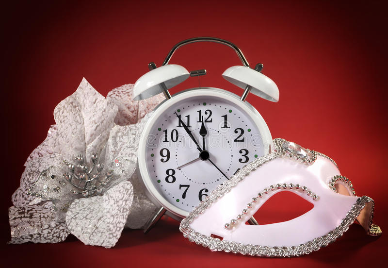 Happy New Year clock, masquerade party mask and festive white flowers royalty free stock photography
