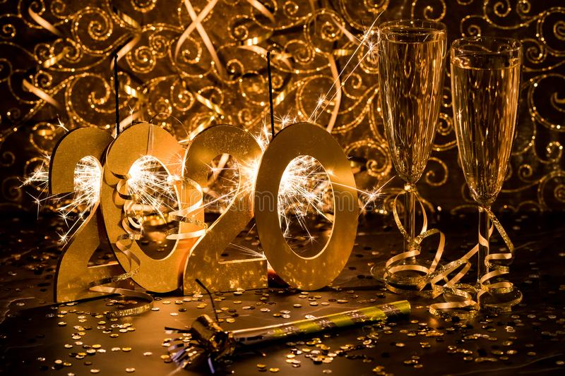 Happy New Year 2020. Close up creative with wine glasses, ribbons and sparklers all in gold royalty free stock photo