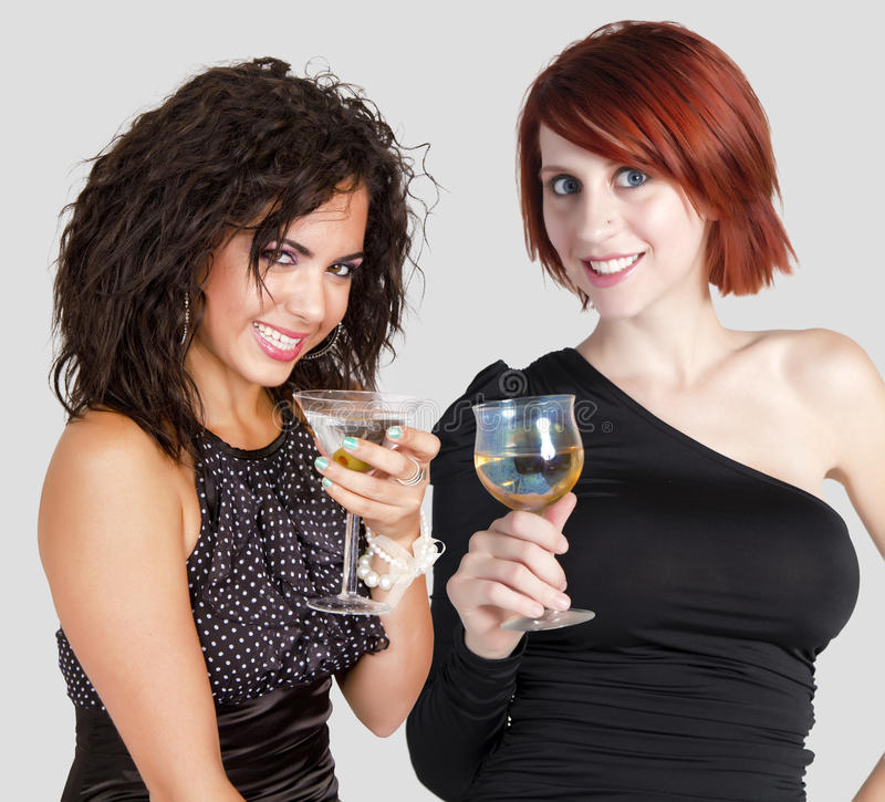 Happy New Year cocktail celebration. Beautiful young brunette woman and redhead woman toasting at happy New Year cocktail celebration stock photography