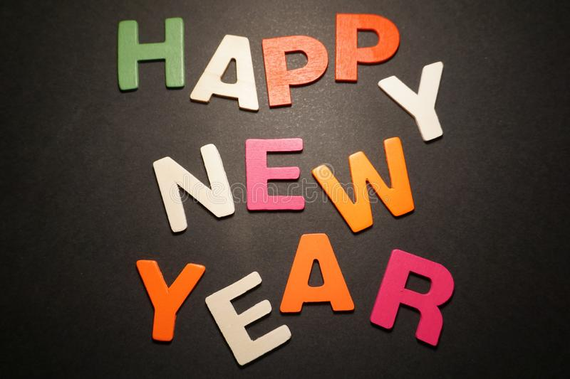Happy New Year. Color letters on black background text illustration message creative type graphic pedryj royalty free stock photo