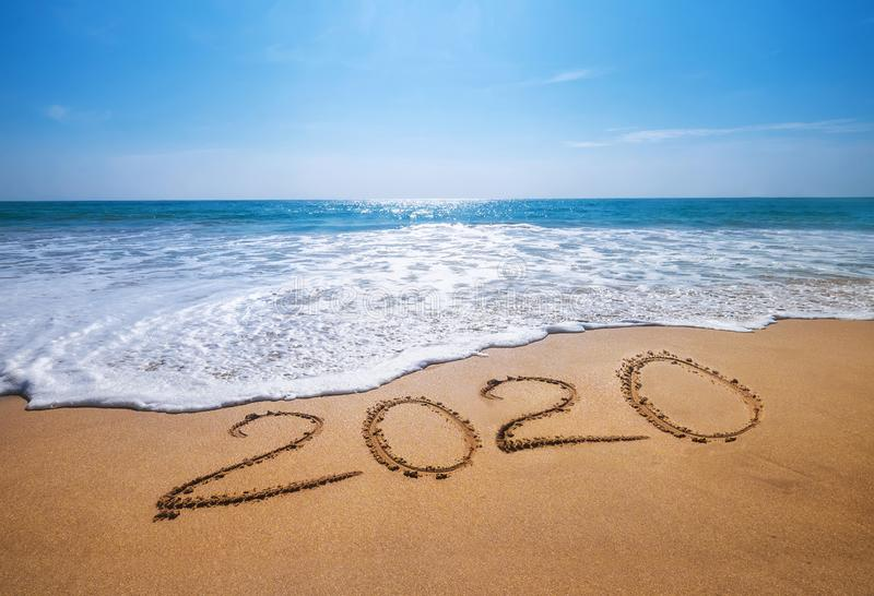 Happy New Year 2020 is coming concept sandy tropical ocean beach lettering. Exotic New Year celebration concept image royalty free stock photo
