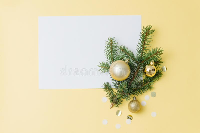Happy new year composition. Paper sheet, fir branch with decorations over yellow stock photos