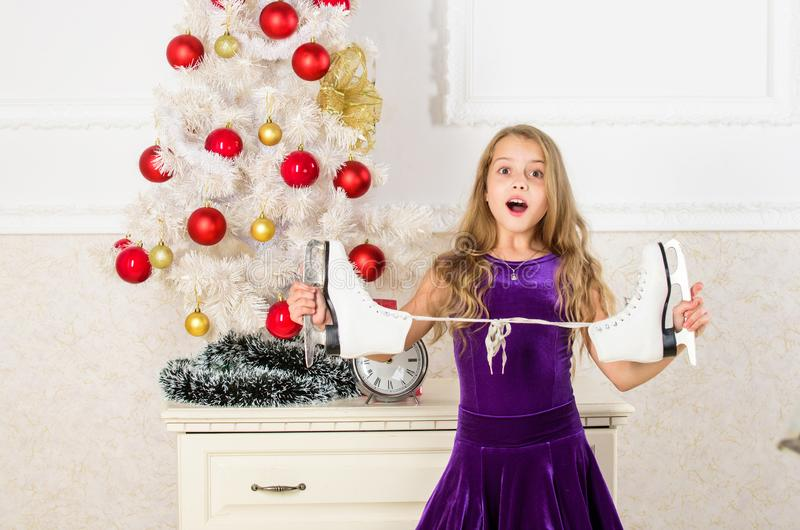 Happy new year concept. Dreams come true. Got gift exactly she wanted. Figure skating concept. Kid near christmas tree. Hold skates gift. Little girl satisfied royalty free stock photography