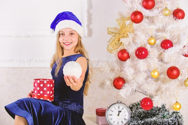 Happy new year concept. Kid girl sit near christmas tree hold gift box. Little girl santa hat excited about christmas. Gift or present. Child celebrate royalty free stock photos