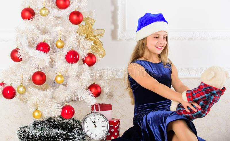 Happy new year concept. Kid sit near christmas tree hold teddy bear gift. Excitement replaced with strong feeling stock image