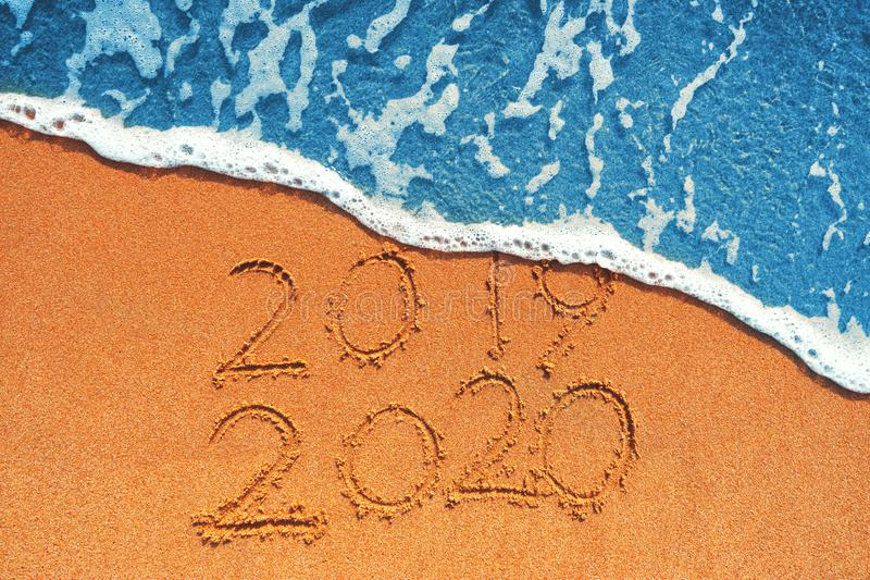 Happy New Year 2020 concept, lettering on the beach. Sea sunrise stock image