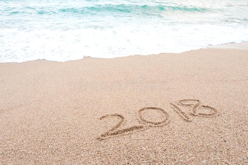 Happy new year 2018 concept. Number 2018 written on sandy beach stock image