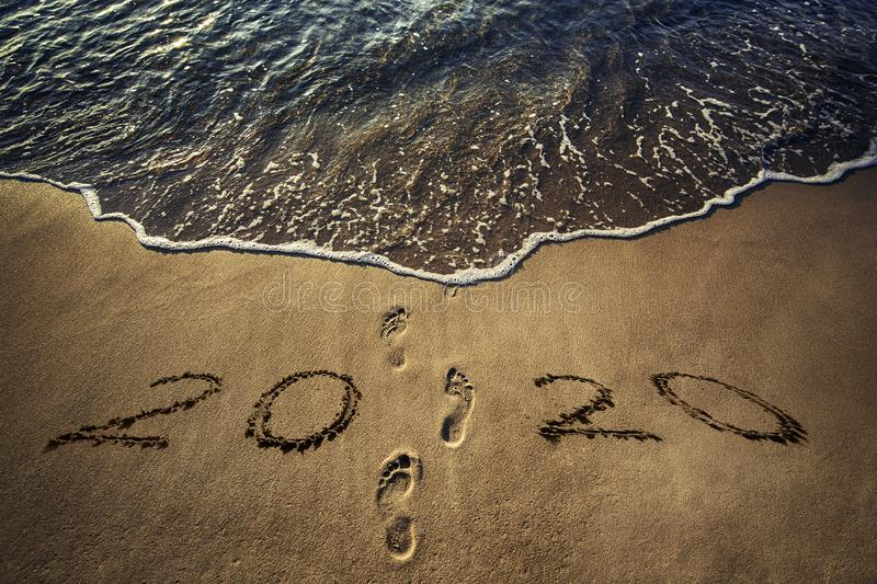 Happy New Year 2020 concept on the sea beach at sunrise. Happy New Year 2020 concept written on the sea beach at sunrise royalty free stock photo
