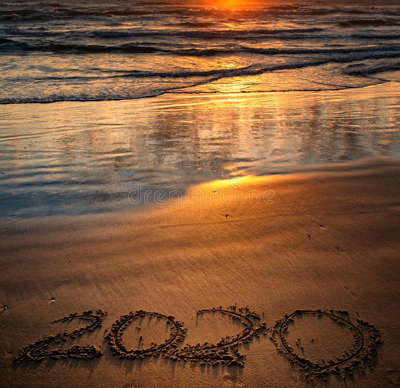 Happy New Year 2020. Concept, on the sea beach at sunset royalty free stock photography