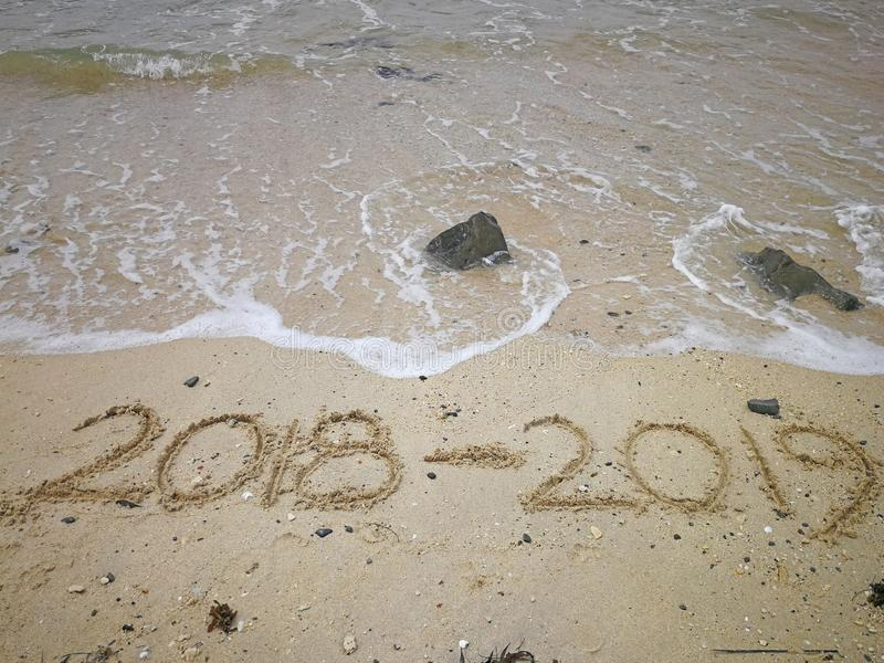 Happy new year concept, 2018 to 2019 written in the sand on a beach stock photo