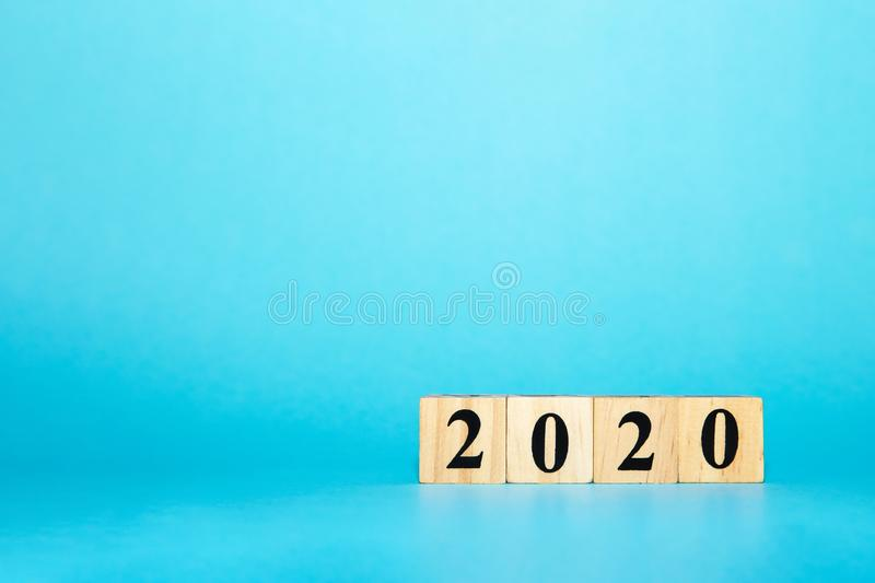 Happy New year concept. Wooden block cube of 2020 year number on blue isolate background stock photography