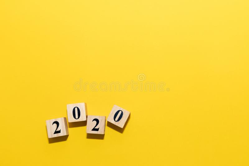 Happy New year concept with Wooden block cube of 2020 year number on yellow isolate background royalty free stock images