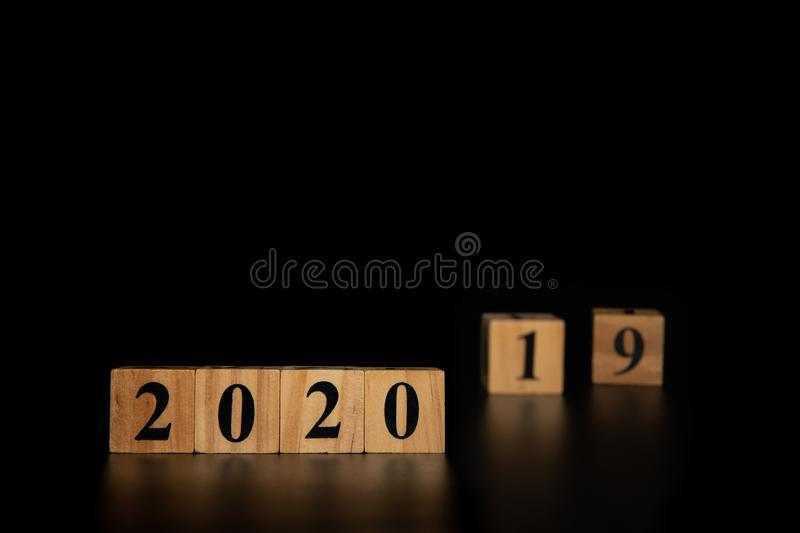 Happy New year 2020 concept with wooden cube change from 2019 to 2020 on black background stock photos