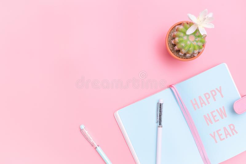Happy New Year concept, workspace desk styled design office supplies and cactus on pink pastel background minimal style royalty free stock image