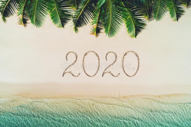Happy new year concept, 2020 written on the sand. Summer holiday on tropical island. Palm trees and sea waves stock image