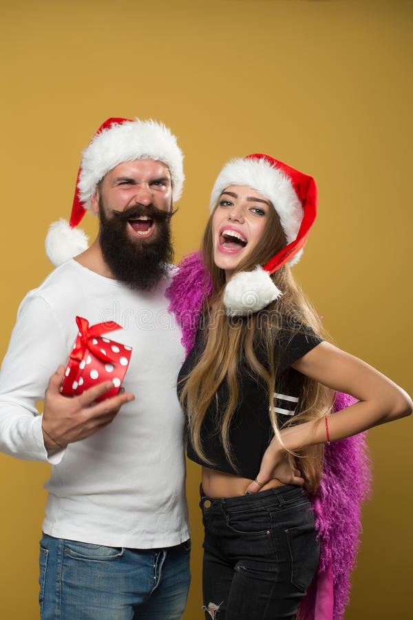 Happy new year couple. Young beautiful happy new year couple of men with long beard with present box and women in red santa christmas hat with fur in studio on royalty free stock photo