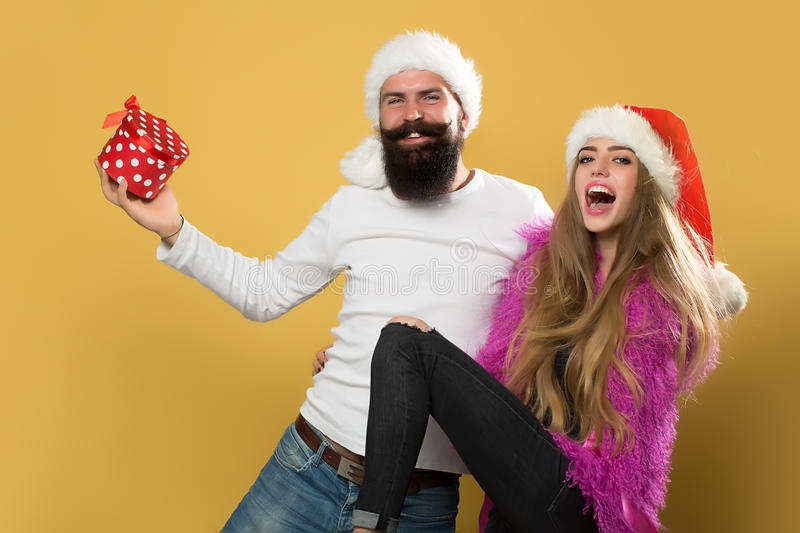 Happy new year couple. Young beautiful happy new year couple of men with long beard with present box and women in red santa christmas hat with fur in studio on royalty free stock photography
