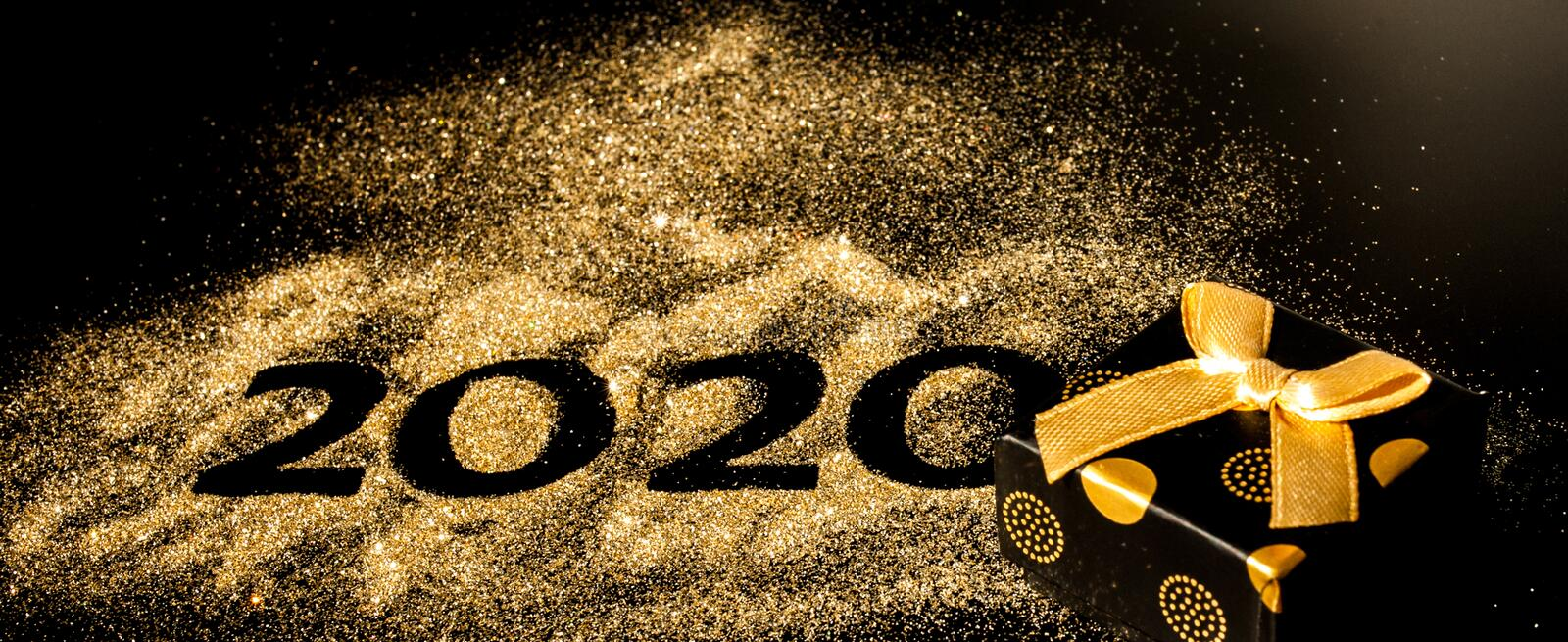 Happy New Year 2020 . Creative Collage of numbers two and zero made up the year 2020. Beautiful sparkling Golden number 2020 and. Gift on black background for stock photos
