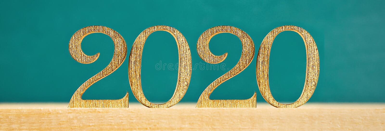 Happy New Year 2020. Creative text Happy New Year 2020 written in gold wooden letters. Banner stock photo