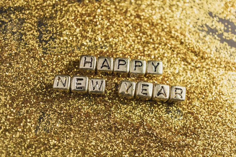 Happy new year cube on glitter gold, holiday glowing abstract background stock images