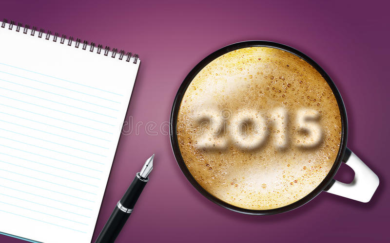 Happy New year. 2015, cup of cappuccino with 2015 numbers made from foam with notepad and pen royalty free stock photo