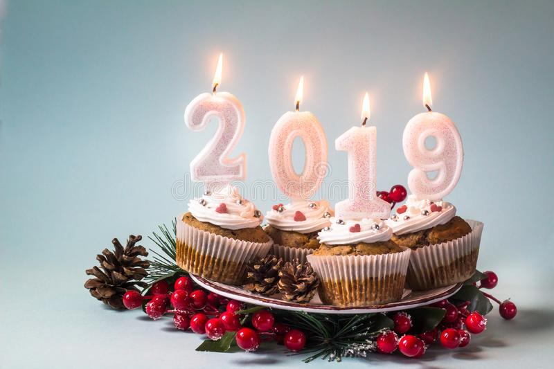Happy New Year 2019 cupcakes with lighting candles. stock photos
