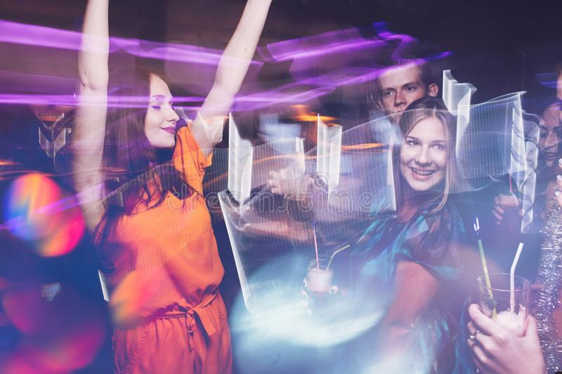 Happy New Year dance party in motion. Joyful friends company in night club, active Christmas celebration. Disco people in blurred colors, modern youth life royalty free stock photos