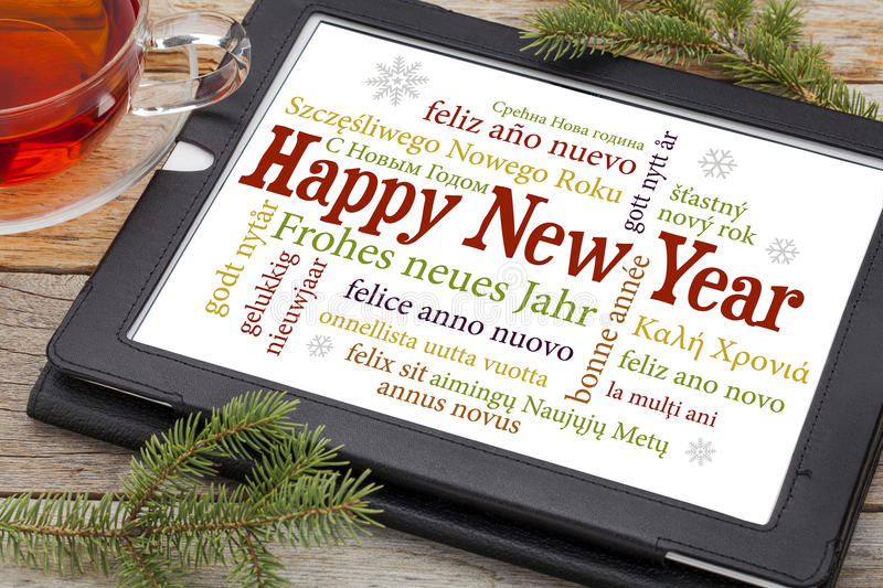 Happy New Year. In different languages on a digital tablet with a cup of tea and spruce twigs stock photography