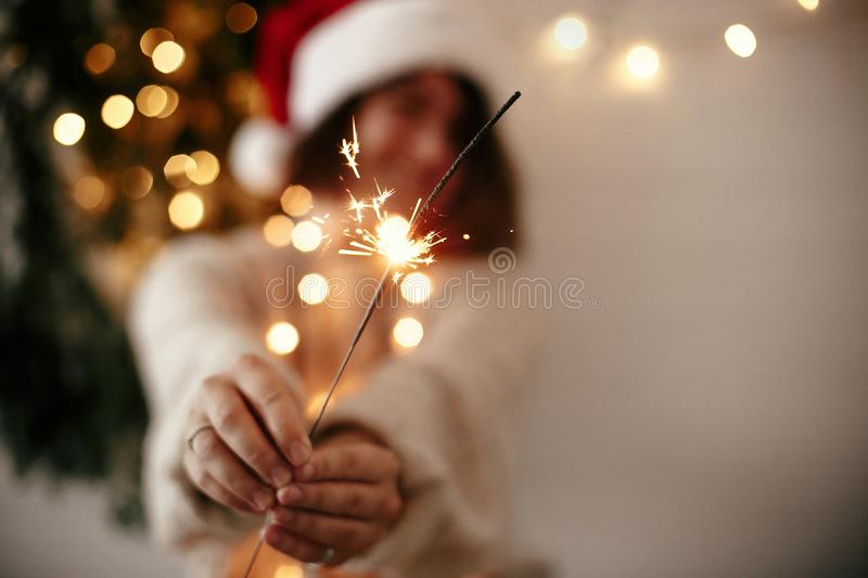 Happy New Year eve party atmosphere. Sparkler burning in hand of stylish girl in santa hat on background of modern christmas tree. Light in dark room. Woman royalty free stock photography