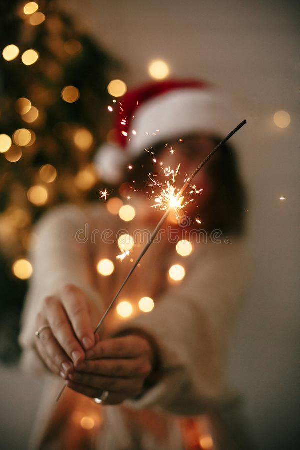 Happy New Year eve party atmosphere. Sparkler burning in hand of stylish girl in santa hat on background of modern christmas tree. Light in dark room. Woman stock photo