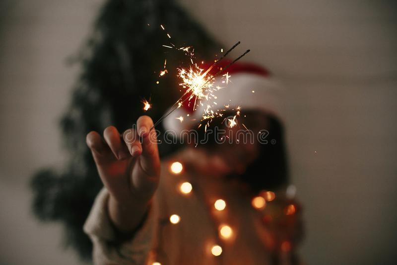 Happy New Year eve party atmosphere. Sparkler burning in hand of stylish girl in santa hat on background of modern christmas tree royalty free stock images