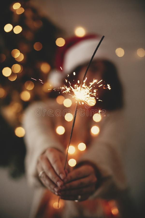 Happy New Year eve party atmosphere. Sparkler burning in hand of stylish girl in santa hat on background of modern christmas tree. Light in dark room. Woman stock photos
