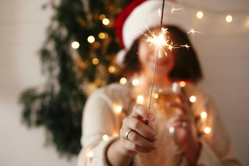 Happy New Year eve party atmosphere. Sparkler burning in hand of stylish girl in santa hat on background of modern christmas tree. Light in dark room. Woman stock images