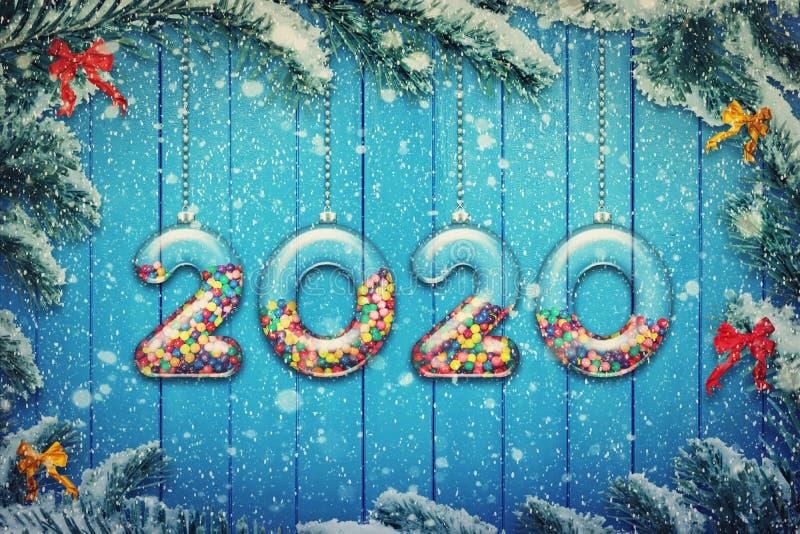 Happy New Year 2020 Feiertage Hintergrund Transparente Zahlen aus Glas mit buntfarbenen Süßwaren und Süßigkeiten hängen an einem  lizenzfreie stockbilder