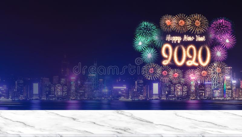 Happy new year 2020 fireworks over cityscape at night with empty marble table top,Panoramic banner mock up template for display or. Montage of product for royalty free stock photography