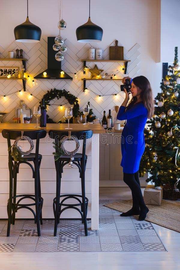 Happy New Year. Girl takes pictures of New Year decorations in the kitchen decorated for the New stock photo