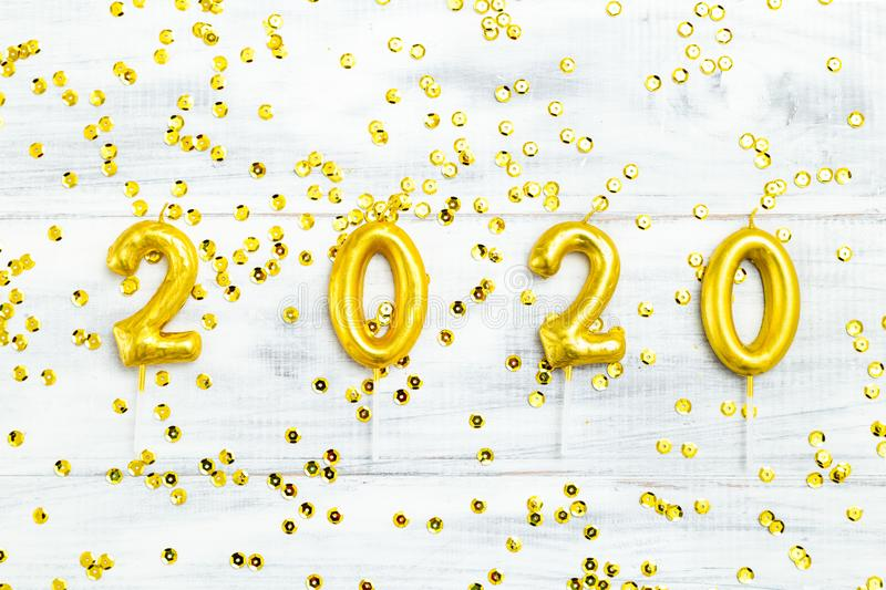 Happy New Year 2020 gold numbers on white wooden background and golden sparkle. Flat lay. Happy New Year 2020 gold numbers on white wooden background and golden stock images